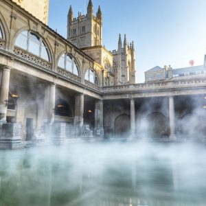 Picture of interior of Roman baths with steam rising off the water, Bath, England
